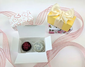 A variety of 2 chocolate ballotin boxes with ribbons