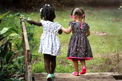 Two little girls walking together in garden. A friendship portray.