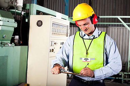 HSE inspector with hat and cipboard in a factory
