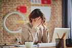 mental wellbeing woman sat at desk stressed