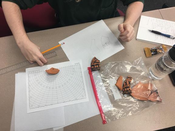 Students drawing their broken vases