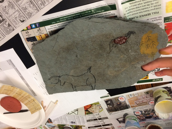 """Students making """"cave paintings"""" using a stone slab and ochre"""