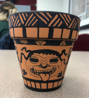 A student's recreation of the ancient Greek Vase painting activity (a vessel painted with a Medusa face)