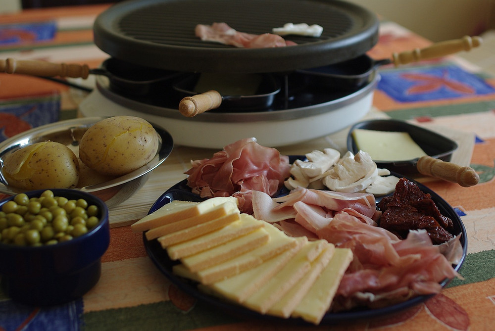 Picture showing the raclette machine, cheese, ham and other sides