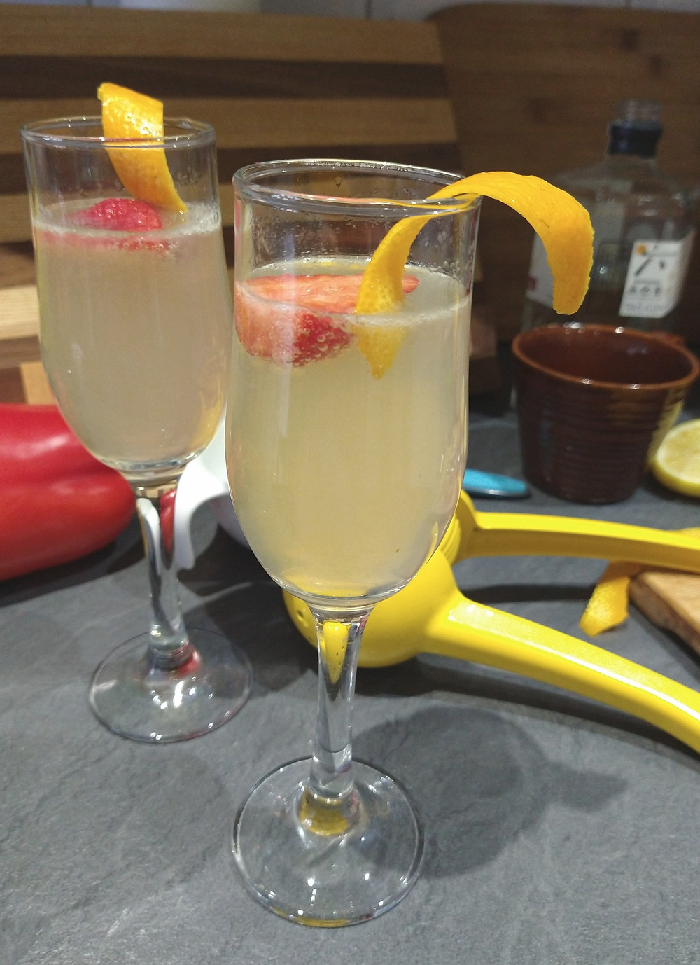 Picture of the French 75 cocktail, served and garnished with a strawberry and orange twist