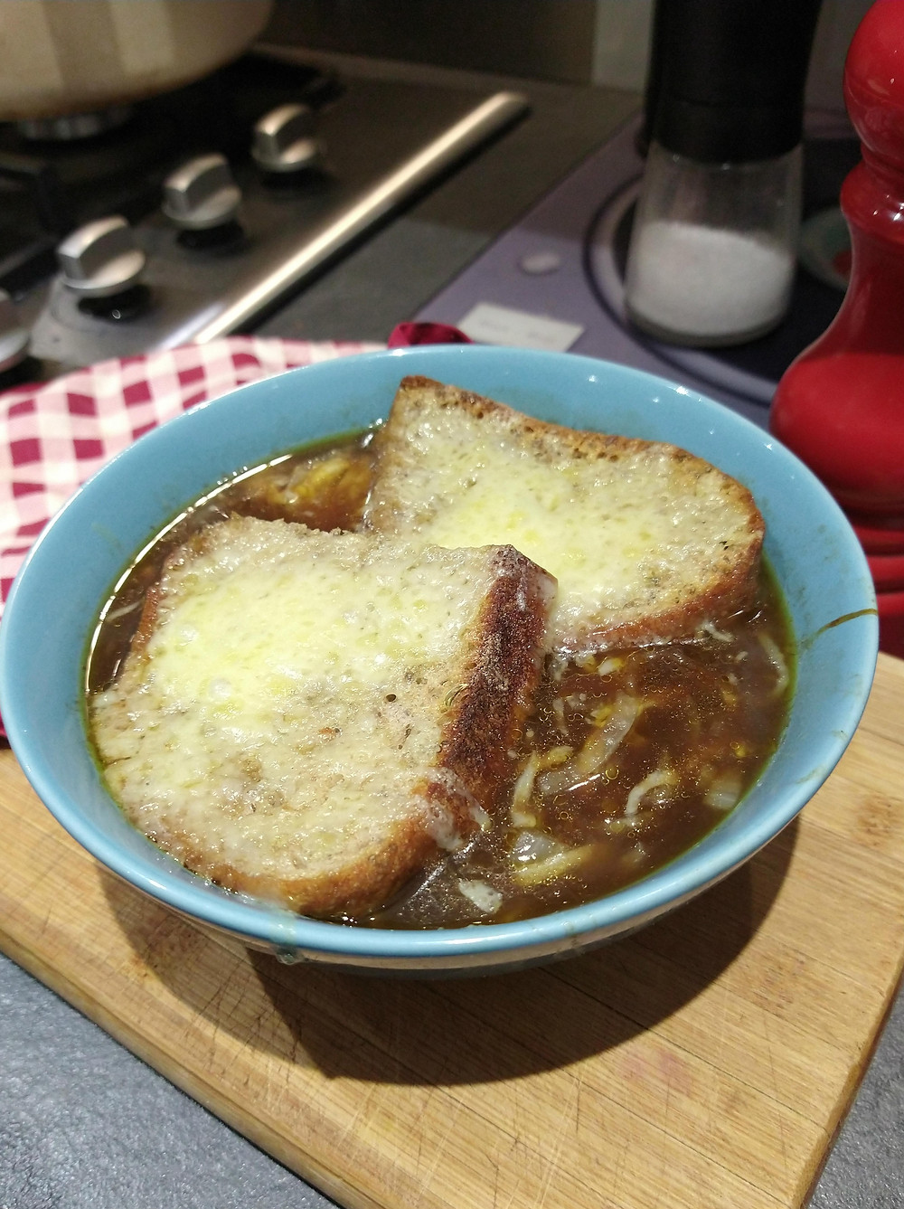 Photo of French onion soup topped with crusty bread and melted cheese, freshly grilled