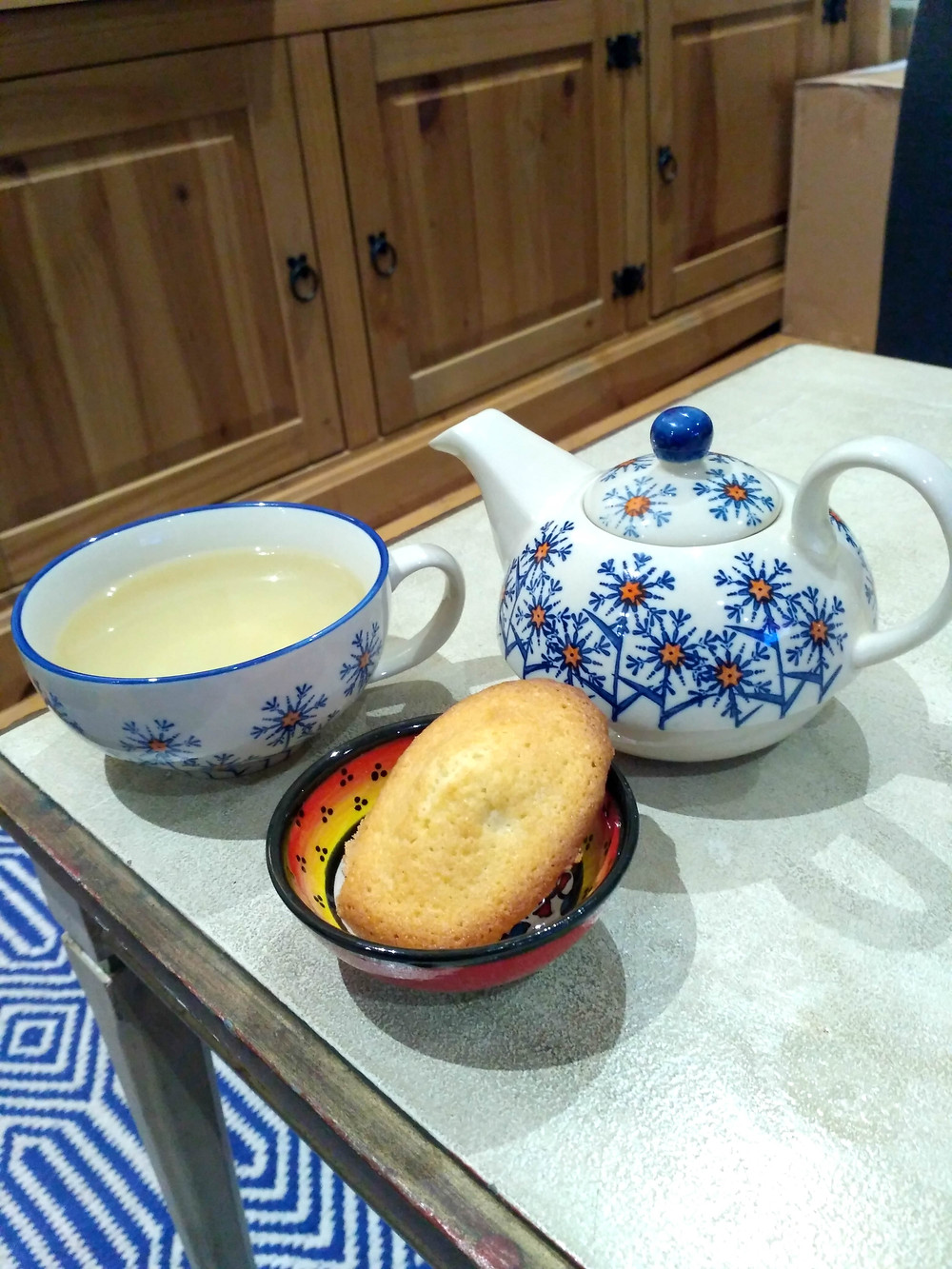 Picture of a single madeleine with a cup of tea
