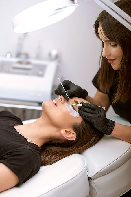 Smiling beautician technician applying eyelash extensions to client