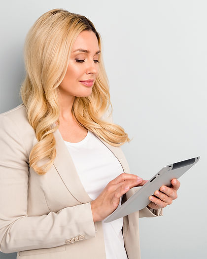 A professional looking woman looking down smiling at a tablet to show how Bookwell can be accessed on any device and give business owners more clarity and control