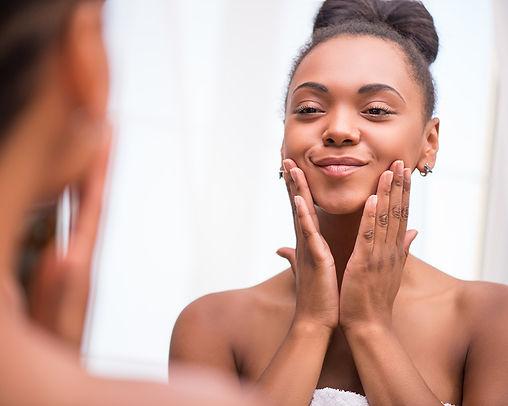 Woman with beautiful skin touching her f