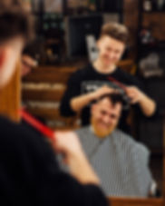 Barber smiling with laughing client in barbershop
