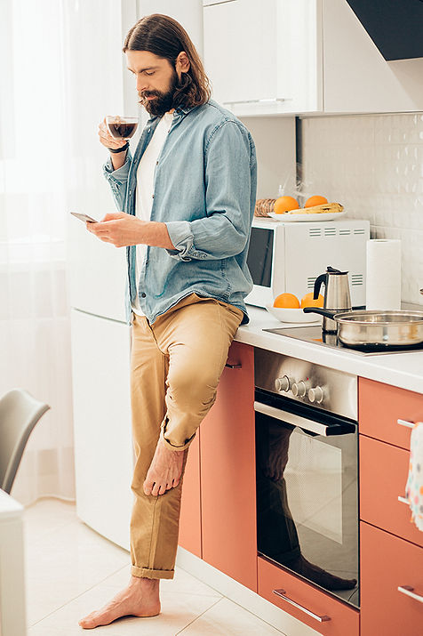 Business man waking up to new Bookwell bookings looking at phone in kitchen with coffee