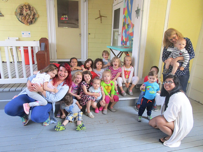 Families with Young Children Retreat, kids and staff sit on porch step next to kitchen entrance