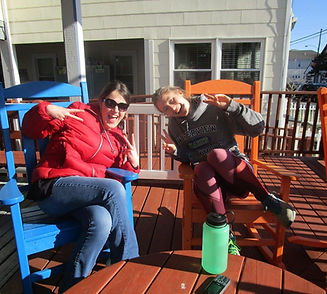Young Adult Retreat, 2 girls sitting on porch with goofy faces and showing the peace sign.
