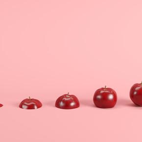 Slices of fresh, red apple on pink backg