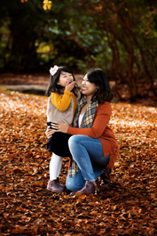 Mother and toddler daughter dressed in warm autumn clothing laughing in the leaves at Queen Elizabeth Park in Vancouver.