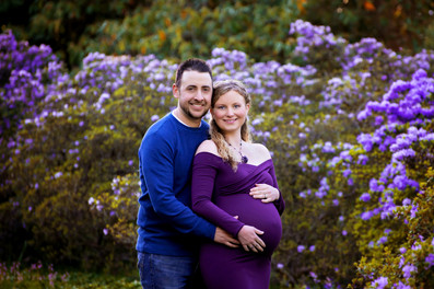 Pregnant woman wearing a long sleeve grape purple maternity gown with husband standing on a path surrounded by purple flowers at Deer Lake Park in Burnaby | Maternity Photographer Vancouver | Amber Theresa Photography