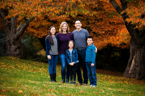 Family of 5 with father, mother, daughters and son standing against the fall trees at Queen Elizabeth Park by Vancouver family photographer Amber Theresa Photography.