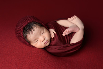 Newborn baby boy in a red wrap and knitted bonnet posed on a garnet red blanket by Vancouver newborn photographer Amber Theresa Photography