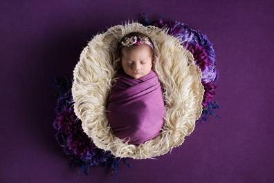 Newborn baby girl in mauve wrap and flower headband laying in a cream basket surrounded by purple flowers by Vancouver newborn photographer Amber Theresa Photography