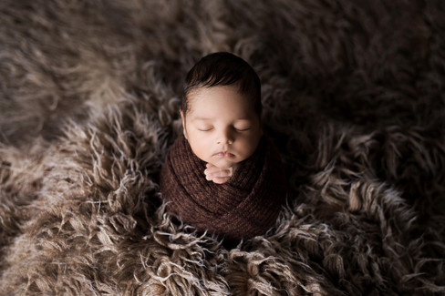 Newborn baby boy in a chocolate brown wrap nestled in a brown fur rug by Vancouver newborn photographer Amber Theresa Photography