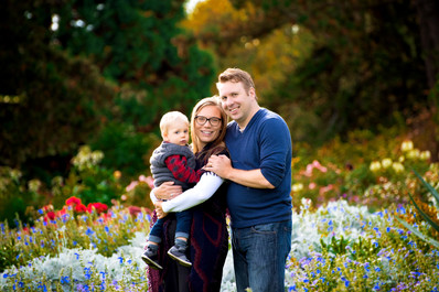 Mother, father and 1 year old son in the rose garden at Queen Elizabeth Park.