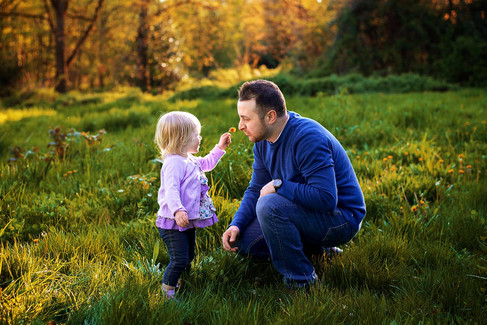 Toddler girl holding flower up to father's nose in a grass field during sunset at Deer Lake Park in Burnaby.