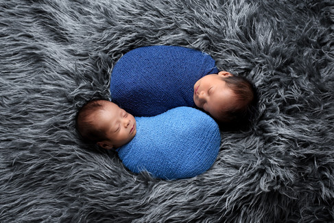 Newborn baby boy twins in blue wraps posed in a yin and yang position on a grey faux flokati rug by Vancouver newborn photographer Amber Theresa Photography