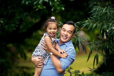 Father holding toddler daughter for family photoshoot outdoors at Queens Park in New Wesminster, BC.