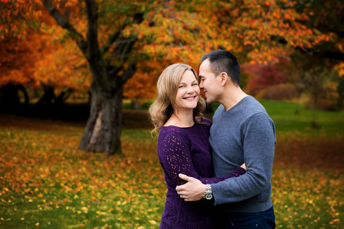 Husband and wife snuggling surrounded by fall leaves in Queen Elizabeth Park by Vancouver family photographer Amber Theresa Photography.