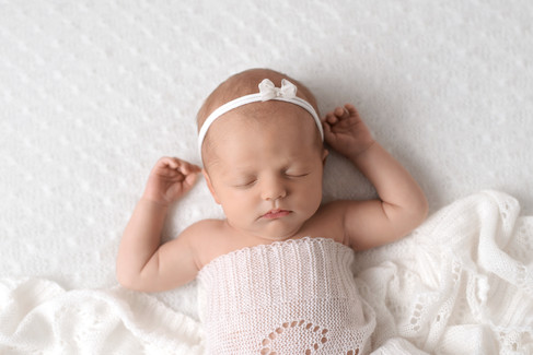 Newborn baby girl in white knit wrap sleeping with arms up by Vancouver newborn photographer Amber Theresa Photography