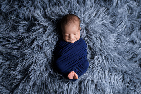 Newborn baby boy smiling in a navy blue wrap on a dark grey fur flokati rug by Vancouver newborn photographer Amber Theresa Photography
