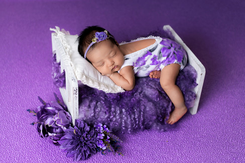 Newborn baby girl in lilac and purple posed on a white wood bed by Vancouver newborn photographer Amber Theresa Photography