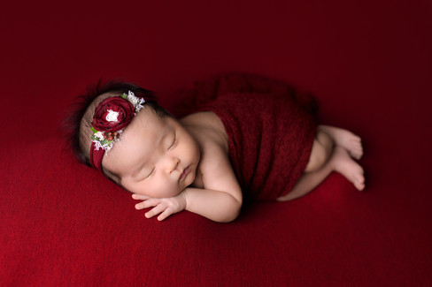 Newborn baby girl in red headband and wrap laying on a dark red blanket with hand under cheek.