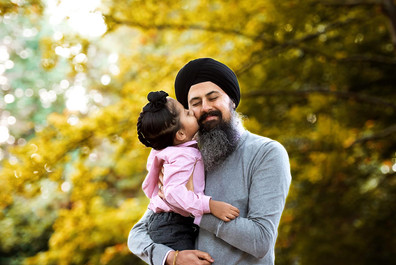 Toddler son kissing father on the cheek at Queen Elizabeth Park in Vancouver.