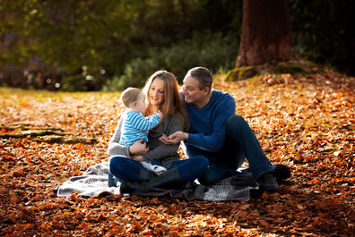 Mother, father and 11 month old baby boy sitting in the fall leaves on a blanket at Queen Elizabeth Park in Vancouver.