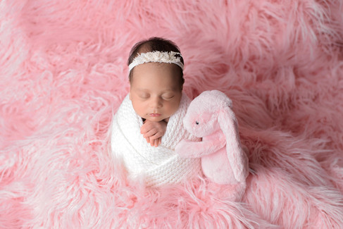 Newborn baby girl in white knit wrap and white headband in potato sack pose on a soft pink fur blanket being hugged by her pink bunny toy by Vancouver newborn photographer Amber Theresa Photography