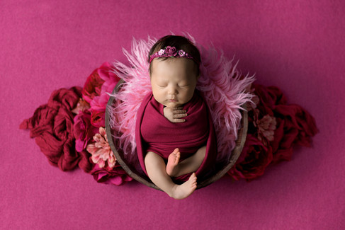 Newborn baby girl in a pink wrap posed in a bucket accented with flowers by Vancouver newborn photographer Amber Theresa Photography