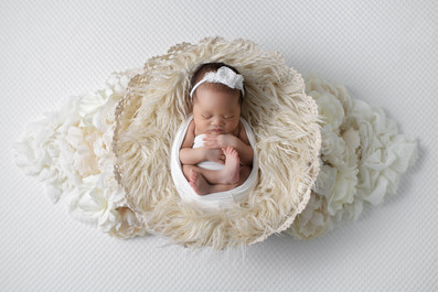 Newborn baby girl in white wrap and headband laying in a cream fur lace basket surrounded by Vancouver newborn photographer Amber Theresa Photography
