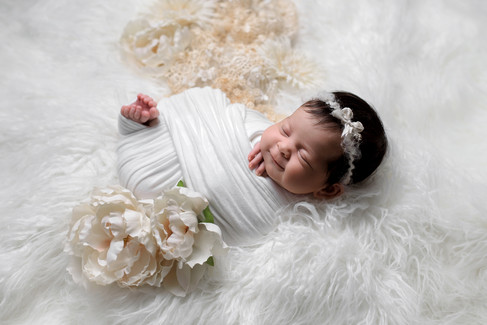 Newborn baby girl with toes and fingers peeking out of wrap smiling on a white fur with flowers by Vancouver newborn photographer Amber Theresa Photography