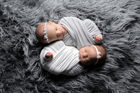 Newborn baby girl twins in white and grey wraps with toes peeking out on a dark grey fur rug by Vancouver newborn photographer Amber Theresa Photography