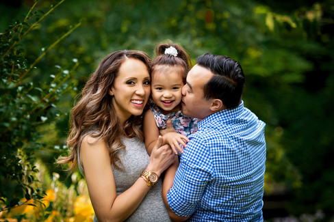 Mother and father holding toddler daughter for family photoshoot outdoors at Queens Park in New Wesminster, BC.