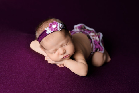 Newborn baby girl wearing a berry purple floral romper \with hands under chin on pink white blanket by Vancouver newborn photographer Amber Theresa Photography