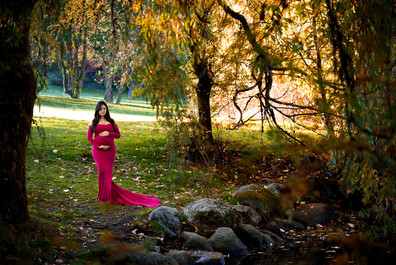 Pregnant woman wearing a long sleeve magenta maternity gown in the fall leaves by the duck pond at Queen Elizabeth Park in Vancouver | Maternity Photographer Vancouver | Amber Theresa Photography
