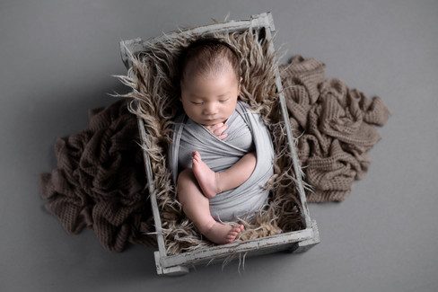 Newborn baby boy in a grey wrap laying in a brown fur crate bed by Vancouver newborn photographer Amber Theresa Photography