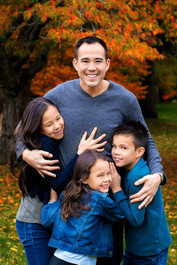 Father and three children smiling and hugging by fall leaves in Queen Elizabeth Park by Vancouver family photographer Amber Theresa Photography.