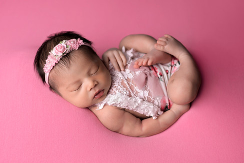 Newborn baby girl wearing white and pink romper with flower headband in Huck Finn pose on a pink blanket  by Vancouver newborn photographer Amber Theresa Photography