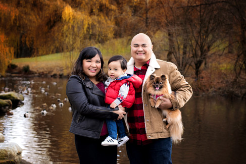 Mother, father, 1 year old toddler and dog standing in front of the duck pond at Queen Elizabeth Park by Vancouver family photographer Amber Theresa Photography.