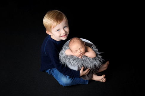 3 year old toddler brother holding newborn baby boy in a grey bucket with hands under chin by Vancouver newborn photographer Amber Theresa Photography