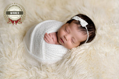 Newborn baby girl in white knit wrap and bow headband laying in cream fur by Vancouver newborn photographer Amber Theresa Photography